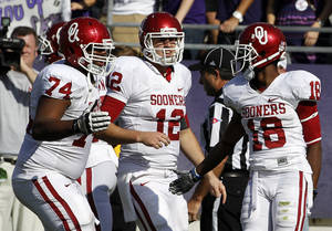 Photo - Oklahoma's Adam Shead (74), Landry Jones (12) and Jalen Saunders (18) celebrate Saunders' touchdown reception against TCU in the first half of an NCAA college football game Saturday, Dec. 1, 2012, in Fort Worth, Texas. (AP Photo/Tony Gutierrez)