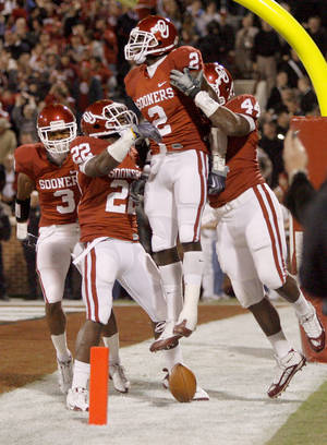 Photo - OU's Brian Jackson celebrates with Jonathan Nelson, left, Keenan Clayton, and Jeremy Beal after Jackson returned a fumble for a touchdown during the Big 12 college football game between the University of Oklahoma Sooners and the Texas A&M Aggies at Gaylord Family - Oklahoma Memorial Stadium in Norman, Okla. Photo by Bryan Terry, The Oklahoman