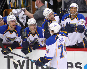 Photo - St. Louis Blues right wing T.J. Oshie (74) is congratulated by the bench after scoring on Minnesota Wild goalie Ilya Bryzgalov (30) in the shoot out during their NHL hockey game Sunday, March 9, 2014 in St. Paul, Minn.. The Blues defeated the Wild 3-2 in a shootout.(AP Photo/Andy Clayton-King)