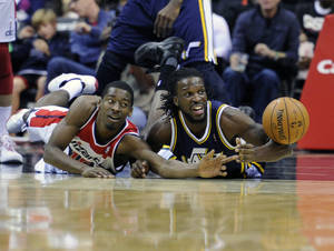 photo -   Washington Wizards&#039; Jordan Crawford, left, fights for the ball against Utah Jazz&#039;s DeMarre Carroll, right, during the first half of an NBA basketball game, Saturday, Nov. 17, 2012, in Washington. (AP Photo/Nick Wass)  