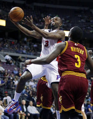 Photo - Detroit Pistons guard Rodney Stuckey, left, goes to the basket past Cleveland Cavaliers guard Dion Waiters, right, during the first period of an NBA basketball game Wednesday, March 26, 2014, in Auburn Hills, Mich. (AP Photo/Duane Burleson)
