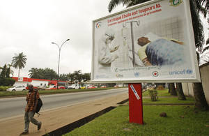 Photo - A man, left, walk past a Ebola awareness campaign poster, in the city of Abidjan, Ivory Coast,  Monday, Aug. 25, 2014. (AP Photo/Sevi Herve Gbekide )