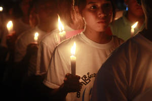 Photo -   Protesters hold candles during a candlelight vigil in Yangon, Myanmar Friday, May 25, 2012. (AP Photo/Khin Maung Win)