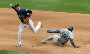 Photo - Colorado Rockies shortstop Troy Tulowitzki, left, throws to first base after forcing out Los Angeles Dodgers' Yasiel Puig at second base on the front end of a double play hit into by Adrian Gonzalez to end the top of the fourth inning of a baseball game in Denver on Saturday, June 7, 2014. (AP Photo/David Zalubowski)