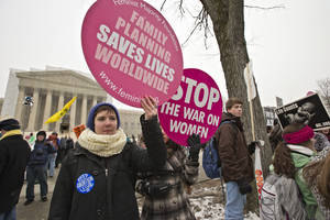 photo - Abortion rights protesters hold signs as anti-abortion activists march past the Capitol to the Supreme Court in Washington, Friday, Jan. 25, 2013, as they observe the 40th anniversary of the Roe v. Wade decision.  Thousands of anti-abortion demonstrators marched through Washington to the steps of the U.S. Supreme Court to protest the landmark decision that legalized abortion. (AP Photo/J. Scott Applewhite)