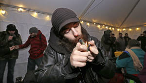 Photo - File-This Dec. 6, 2013, file photo shows Toby Tackett lighting a marijuana joint at a pot party at the Seattle Center, in Seattle. Colorado pot stores open Jan. 1 as retailers open their doors to the nation's first legal recreational pot industry. Sales in Washington, which also legalized recreational marijuana, are expected to start later in the year. (AP Photo/Elaine Thompson, File)