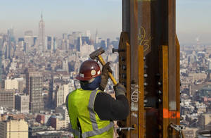 "Photo -   FILE- In this Dec. 16, 2010, file photo, an ironworker connects a steel plate to a column at One World Trade Center in New York. The Empire State Building is visible in the rear upper left. One World Trade Center, the giant monolith being built to replace the twin towers destroyed in the Sept. 11 attacks, will lay claim to the title of New York City's tallest skyscraper on Monday, April 30, 2012, as workers erect steel columns that will make its unfinished skeleton a little over 1,250 feet, just high enough to peak over the observation deck on the Empire State Building. The milestone is a preliminary one. The so-called ""Freedom Tower"" isn't expected to reach its full height for at least another year, at which point it is likely to be declared the tallest building in the U.S. (AP Photo/Mark Lennihan, File)"