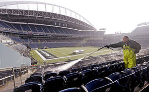 Photo - A worker, who declined to be identified, cleans seats at CenturyLink Field in preparation for the NFL football NFC championship in Seattle, Wednesday, Jan. 15, 2014. The Seattle Seahawks play the San Francisco 49ers on Sunday. (AP Photo/Elaine Thompson)