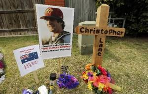 Photo - A memorial to Christopher Lane has developed on Country Club Road on Tuesday, Aug. 20, 2013 in Duncan, Okla. Flowers posters and a cross mark the scene where he was shot and killid. Photo by Steve Sisney