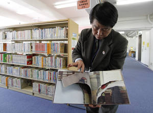 "Photo - A ripped copy of Anne Frank's ""Diary of a Young Girl"" picture book is shown by Shinjuku City Library Director Kotaro Fujimaki at the library in Tokyo Friday, Feb. 21, 2014. Tokyo Libraries said on Friday that hundreds of copies of Anne Frank's diary and related books have been found vandalised across the city's libraries in the last month, sparking fears of an anti-Semitic motive. A total of 265 books in 31 libraries had been found damaged after the first damaged book was found in January, prompting a wider search. (AP Photo/Koji Ueda)"