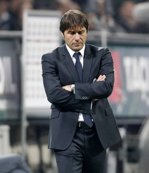 "photo -   FILE - In this Feb. 25, 2012 file photo, Juventus coach Antonio Conte walks on the pitch during a Serie A soccer match in Milan, Italy. Antonio Conte had his 10-month suspension for match-fixing violations extended by FIFA on Friday to include all matches worldwide, barring him from working at a Champions League game against Chelsea next week. Conte's ban ""covers all types of matches, including domestic, international, friendly and official fixtures,"" FIFA said in a statement. Juventus, a two-time European champion, begins the Champions League group stage away to titleholder Chelsea on Wednesday. The group also includes Shakhtar Donetsk and Nordsjaelland. (AP Photo/Antonio Calanni, File)"