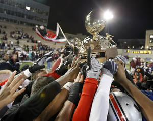Photo - Tulsa Union players hoist their teams' Class 6A championship football trophy following their victory over Jenks at Chapman Stadium, Friday, Dec. 4, 2009, in Tulsa, Okla. (Stephan Holman, Tulsa World)