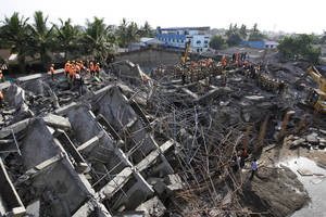 Photo - Rescuers search for workers believed buried in the rubble of a building that collapsed on the outskirts of Chennai, India, Sunday, June 29, 2014. Police said dozens of workers have been pulled out so far and the search is continuing. (AP Photo/Arun Sankar K)