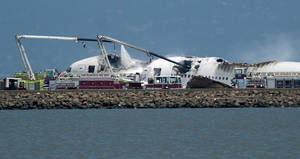Photo - A fire truck sprays water on Asiana Flight 214 after it crashed at San Francisco International Airport on Saturday, July 6, 2013, in San Francisco. (AP Photo/Noah Berger)
