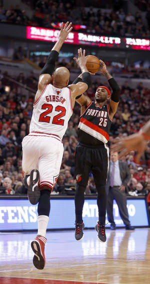 Photo - Portland Trail Blazers guard Mo Williams (25) shoots as Chicago Bulls forward Taj Gibson (22) defends during the first half of an NBA basketball game Friday, March 28, 2014, in Chicago. (AP Photo/Charles Rex Arbogast)