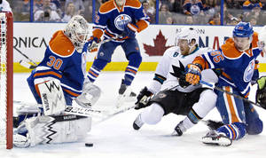 Photo - San Jose Sharks Joe Pavelski (8) is stopped by Edmonton Oilers goalie Ben Scrivens (30) as Martin Marincin (85) tries to defend during the first period of an NHL hockey game in Edmonton, Alberta, on Wednesday, Jan. 29, 2014. (AP Photo/The Canadian Press, Jason Franson)