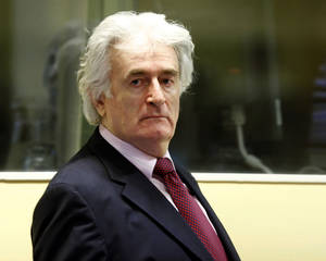 Photo -   FILE - In this Nov. 3, 2009 file photo former Bosnian Serb leader Radovan Karadzic enters the courtroom of the U.N.'s Yugoslav war crimes tribunal (ICTY) in The Hague, Netherlands. The ICTY has acquitted Karadzic of one of the two genocide charges he faces at the halfway stage of his long-running trial on Thursday, June 28, 2012. Judges say prosecutors did not present enough evidence to support the genocide count covering mass killings, expulsions and persecution by Serb forces of Muslims and Croats from Bosnian towns early in the country's 1992-95 war. (AP Photo/Michael Kooren/Pool, File)