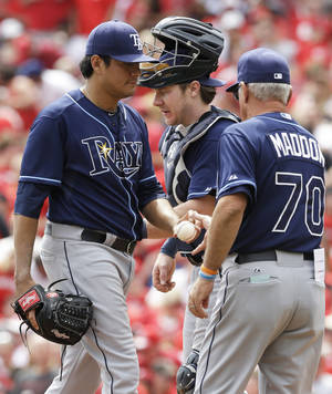 Photo - Tampa Bay Rays manager Joe Maddon (70) takes starting pitcher Cesar Ramos, left, out in the third inning of a baseball game against the Cincinnati Reds, Sunday, April 13, 2014, in Cincinnati. Catcher Ryan Hanigan watches. (AP Photo/Al Behrman)