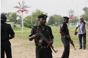"""Photo - Police officers stand guard,  during a rally calling on the Government to rescue the school girls kidnapped from the Chibok Government secondary school in Abuja, Nigeria, Sunday May 11, 2014. The failure to rescue the kidnapped girl students who remain captive after some four weeks has attracted mounting national and international outrage, and one of the teenagers who escaped from the Islamic extremists who abducted the hundreds of schoolgirls, science student Sarah Lawan said Sunday in an interview with The Associated Press the kidnapping was """"too terrifying for words"""". (AP Photo/Sunday Alamba)"""