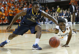 Photo - Oklahoma State guard Stevie Clark (5) dives for the ball in front of West Virginia guard Juwan Staten (3) in the first half of an NCAA college basketball game in Stillwater, Okla., Saturday, Jan. 25, 2014. (AP Photo/Sue Ogrocki)