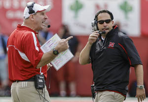 Photo - Nebraska head coach Bo Pelini, left, calls instructions with defensive coordinator John Papuchis looking on, in the first half of an NCAA college football game against UCLA in Lincoln, Neb., Saturday, Sept. 14, 2013. UCLA won 41-21. (AP Photo/Nati Harnik)