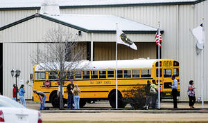 photo - In this Tuesday, Jan 29, 2013 photo, residents look over the school bus where a shooting occurred near Destiny Church along U.S. 231, just north of Midland City, Ala. on Tuesday. Police, SWAT teams and negotiators were at a rural property where a man was believed to be holed up in a homemade bunker Wednesday, HAN 30, 2013 after fatally shooting the driver of a school bus and fleeing with a 6-year-old child passenger, authorities said. The man boarded the stopped school bus in the town of Midland City on Tuesday afternoon and shot the driver when he refused to let the child off the bus. The bus driver died. (AP Photo/The Dothan Eagle, Danny Tindell)