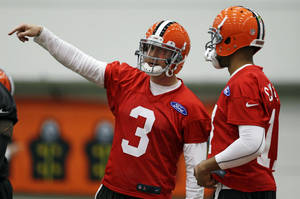 Photo - Cleveland Browns quarterback Brandon Weeden (3) talks with quarterback Jason Campbell during NFL football mini-camp at the team's training facility, Tuesday, April 16, 2013, in Berea, Ohio. Weeden and Campbell threw passes side-by-side as the Browns opened their first mini-camp of the season. The 29-year-old Weeden is the incumbent and started 15 games last year. He was the 22nd overall pick in the 2012 draft. Campbell, 31, was signed as a free agent on March 26. The ninth-year pro appeared in six games last season with the Bears. (AP Photo/Tony Dejak)