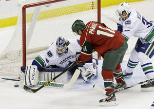 Photo - CORRECTS TO CANUCKS GOALIE CORY SCHNEIDER NOT ROBERTO LUONGO - Vancouver Canucks goalie Cory Schneider, left, stops a shot by Minnesota Wild's Zach Parise (11) as Vancouver Canucks' Henrik Sedin, right, of Sweden, helps defend the net in the first period of an NHL hockey game on Thursday, Feb. 7, 2013, in St. Paul, Minn. (AP Photo/Jim Mone)
