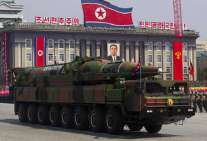 Photo -   FILE - In this April 15, 2012 file photo, a North Korean vehicle carrying a missile passes by during a mass military parade in Pyongyang's Kim Il Sung Square to celebrate the centenary of the birth of the late North Korean founder Kim Il Sung. The enormous, 16-wheel truck used to carry the missile, likely came from China in a possible violation of U.N. sanctions meant to rein in Pyongyang's missile program, experts say. Pinning a sanctions-busting charge on Beijing would be difficult, however, because it would be hard to prove that Beijing provided the technology for military purposes or even that it sold the vehicle directly to North Korea, the experts said. (AP Photo/David Guttenfelder, File)
