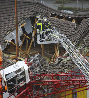 Photo - Firefighters are watching out the site where a crane collapsed and crashed into a supermarket in Bad Homburg, Germany, Wednesday, Dec. 11, 2013. Quoting local police, the German news agency dpa reported that several people had been injured but didn't provide further details. (AP Photo/dpa, Frank Rumpenhorst)