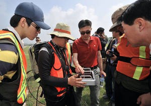 photo - South Korean investigators and technicians discuss a ground-penetrating radar survey of Camp Carroll.