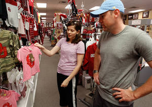 Photo - Right: Joy and Matt Robinson, of Norman, shop for clothes for their daughter Lynlee at Balfour on Campus Corner during a a tax-free weekend.  Photo by Steve Sisney, Oklahoman Archive