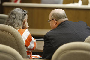 Photo - Murder defendant Rebecca Bryan wipes tears from her face as she talks to her defense attorney,  Gary James, in the Canadian County Courthouse in El Reno.  <strong>Steve Gooch - The Oklahoman</strong>