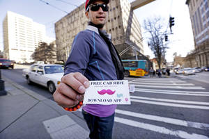 Photo -  Jerad Bernard hands out cards offering one free ride through the Lyft ridesharing service in Seattle.  AP File Photo  <strong>Elaine Thompson -   </strong>