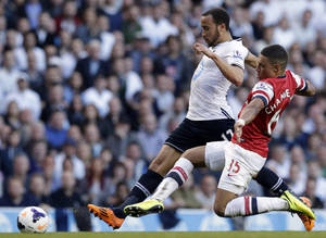 Photo - FILE - In this March 16, 2014, file photo, Tottenham Hotspur's Andros Townsend, left, is challenged for the ball by Arsenal's Alex Oxlade-Chamberlain during the English Premier League soccer match in London. English national team winger Townsend will miss the World Cup because of a left ankle injury. Tottenham said Wednesday, April 30, 2014, the 22-year-old needs surgery to repair damage to ligaments in his left ankle and will be out for 10 weeks. (AP Photo/Matt Dunham, File)