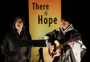 Photo - Louise Goldberg and Mary Reynolds sing during the candlelight vigil in Edmond.