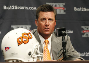 Photo - Oklahoma State University football coach Mike Gundy addresses the media at the beginning of the Big 12 Conference Football Media Days Monday, July 22, 2013 in Dallas.  (AP Photo/Tim Sharp) ORG XMIT: TXTS103