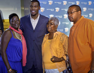 Photo - Kevin Durant poses for a photo with his mother Wanda Pratt, left, grandmother Barbara Davis and father Wayne Pratt after the press conference to officially announce Durant's five-year contract extension. PHOTO BY CHRIS LANDSBERGER, THE OKLAHOMAN