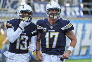 Photo - San Diego Chargers quarterback Philip Rivers, right, and wide receiver Keenan Allen jog off the field together after the pair combined on a 43 yard touchdown pass against the New York Giants during the first half of an NFL football game Sunday, Dec. 8, 2013, in San Diego. (AP Photo/Denis Poroy)