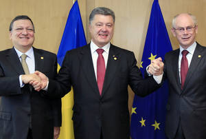 "Photo - Ukraine's President Petro Poroshenko, center, poses with European Commission President Jose Manuel Barroso, left, and European Council President Herman Van Rompuy, right, during an EU Summit in Brussels on Friday, June 27, 2014. Ukrainian President Petro Poroshenko has signed up to a trade and economic pact with the European Union, saying it may be the ""most important day"" for his country since it became independent from the Soviet Union. (AP Photo)"