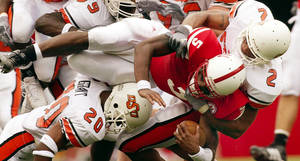 Photo - Oklahoma State University vs. University of Nebraska college football at Memorial Stadium in Lincoln, Neb., Saturday, August 30, 2003. Nebraska quarterback Jammal Lord is tackled at the end of a run by a host of OSU Cowboys including Fath' Carter (2) and Vernon Grant (20) in the first quarter. Staff photo by Nate Billings / The Oklahoman