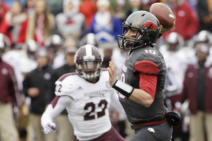 Photo - Arkansas quarterback Brandon Allen (10) passes in front of Mississippi State linebacker Matthew Wells (22) in the first half of an NCAA college football game in Little Rock, Ark., Saturday, Nov. 23, 2013. (AP Photo/Danny Johnston)