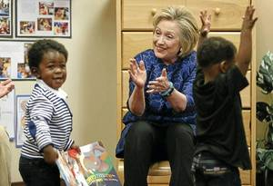 "Photo - Former Secretary of State Hillary Clinton claps for Jaxon Walton (left) after a book-reading at the Tulsa Educare No. 2 site during the kickoff of the ""Talking is Teaching"" campaign on Monday. Photos by MATT BARNARD / Tulsa World"