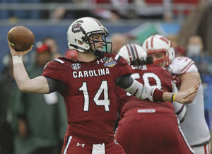 Photo - South Carolina quarterback Connor Shaw (14) throws a pass as he is rushed by Wisconsin defensive end Pat Muldoon, right, during the first half of the Capital One Bowl NCAA college football game in Orlando, Fla., Wednesday, Jan. 1, 2014.(AP Photo/John Raoux)