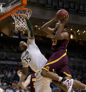 Photo -   Miami's Kenny Kadji (35) is unable to block Minnesota's Rodney Williams from taking a shot during the first half of the second round of the NIT tournament NCAA college basketball game in Coral Gables, Fla., Monday, March 19, 2012. (AP Photo/J Pat Carter)
