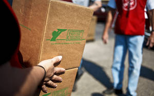 Photo - Volunteers carry boxes to recipients during a Salvation Army and Feed The Children food distribution to families in Oklahoma City. Photo by Chris Landsberger,  The Oklahoman Archives