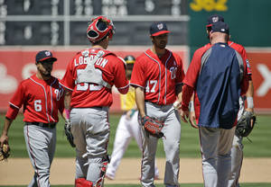 Photo - Washington Nationals starting pitcher Gio Gonzalez, center, is pulled from a baseball game during the fifth inning against the Oakland Athletics, Sunday, May 11, 2014, in Oakland, Calif. (AP Photo/Marcio Jose Sanchez)