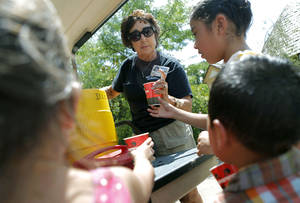 Photo - HEAT / SUMMER WEATHER / CHILD / CHILDREN / KIDS: Pam Allen, an employee at the zoo, passes out free ice and water to Stephanie Hernandez and her family during a hot day at the Oklahoma City Zoo in Oklahoma City on Thursday, July 21, 2011. Photo by John Clanton, The Oklahoman ORG XMIT: KOD