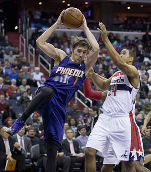 Photo - Phoenix Suns' Goran Dragic (1), of Slovenia, pulls a rebound while Washington Wizards Andre Miller (24) defends during the second half of an NBA basketball game in Washington, Wednesday, March 26, 2014. The Suns won 99-93. (AP Photo/Manuel Balce Ceneta)