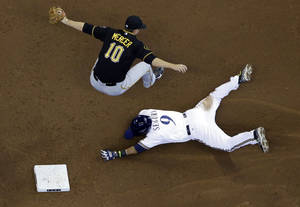 Photo - Pittsburgh Pirates shortstop Jordy Mercer can't handle a high throw as he leaps over Milwaukee Brewers' Jean Segura stealing second during the third inning of a baseball game Thursday, May 15, 2014, in Milwaukee. (AP Photo/Morry Gash)